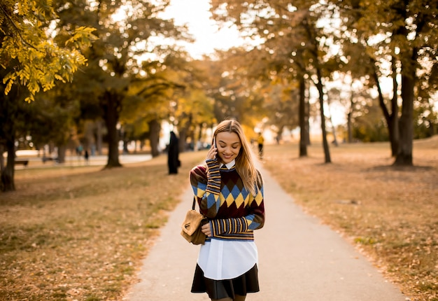 Милая молодая женщина гуляя в парк осени и используя мобильный телефон