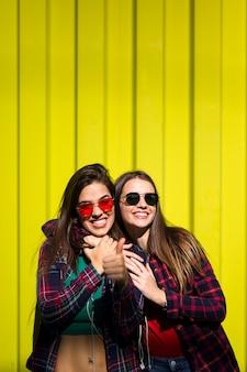 Портрет двух молодых счастливых женщин друзей стоял на открытом воздухе над желтой стеной