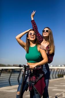 路上で電動スクーターに乗ってかなり若い女性の友人