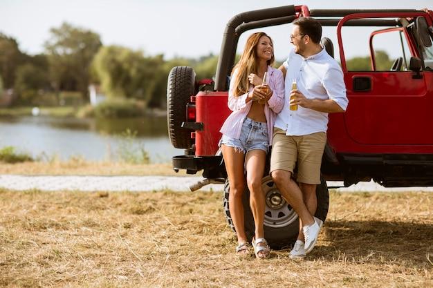 Молодая женщина и мужчина, с удовольствием возле красного автомобиля в летний день