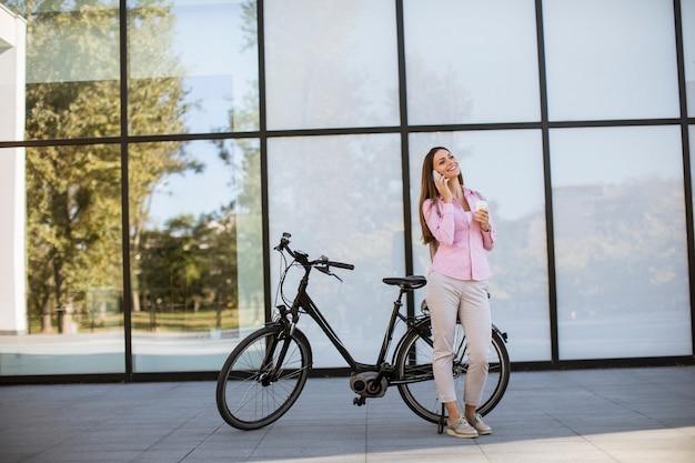 Молодая женщина, с помощью мобильного телефона на современный городской электрический велосипед как чистый устойчивый городской транспорт
