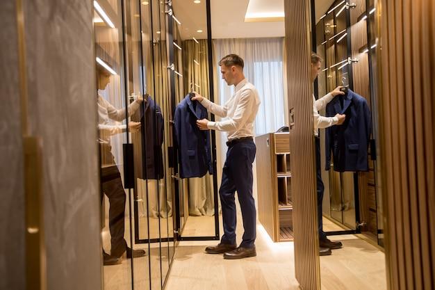 若い男が現代的なアパートのホールでワードローブから服を選ぶ