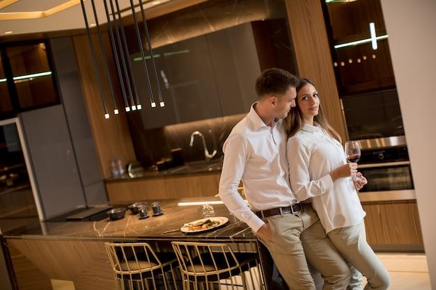 豪華なキッチンでロマンチックなディナーの後、赤ワインを飲んでいる甘いカップル