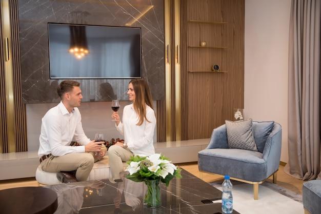 Молодая пара проводит романтический вечер с бокалом красного вина дома в современной гостиной