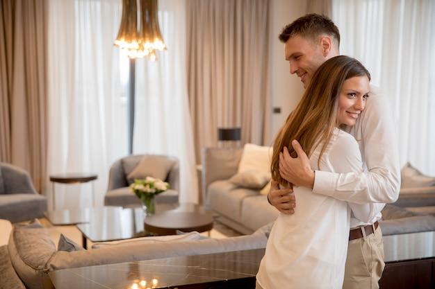 Пара обнимается, стоя в гостиной современной квартиры
