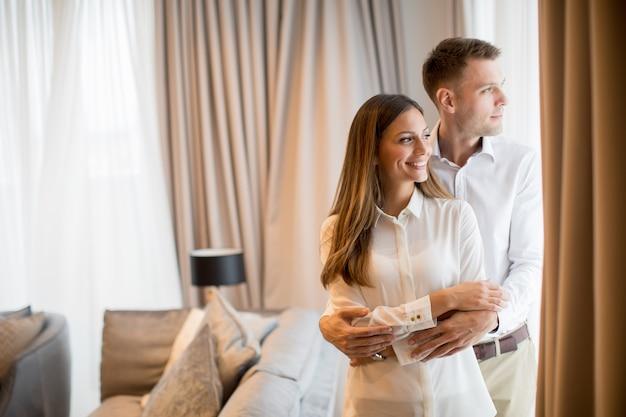 現代的なアパートのリビングルームで立っているを受け入れるカップル