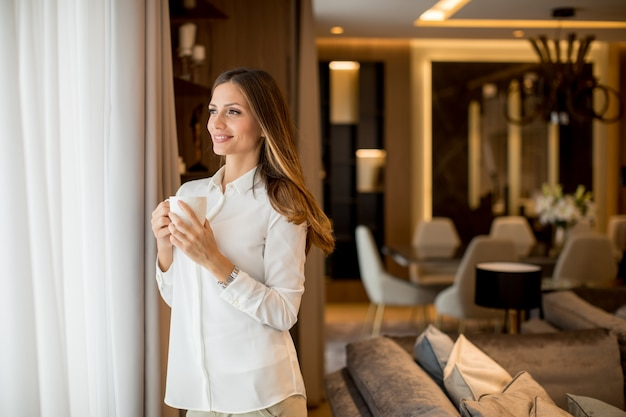 コーヒーを飲みながら、アパートに立ちながら窓から見ている美しい若い女性