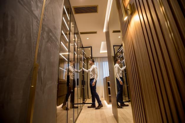 Молодой человек, выбирая одежду из гардероба в зале современной квартиры