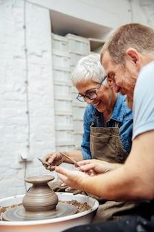 Старшая женщина крутит глину на колесе с учителем в гончарном классе