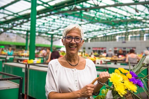 市場で花を買う魅力的な年配の女性