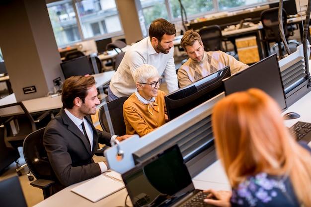 Старший бизнесвумен, работая вместе с молодыми бизнесменами в современном офисе
