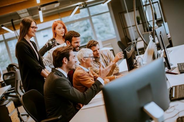 近代的なオフィスに若いビジネス人々と一緒に働くシニアの実業家
