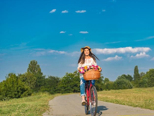 若い笑顔の女性は田舎の花でいっぱいのバスケットで自転車に乗る