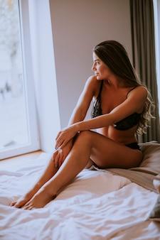 ベッドの上に座っているセクシーな若い女性