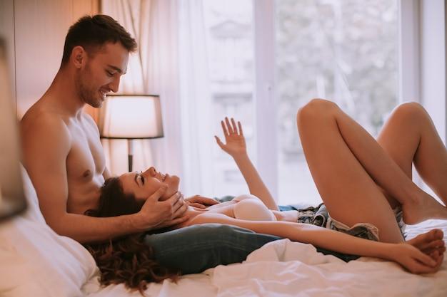 寝室のベッドの上に横たわる若い大人の異性カップル