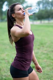 女性のスポーツの後の水を飲む