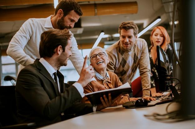 近代的なオフィスの若いビジネス人々と一緒に働くシニアの実業家