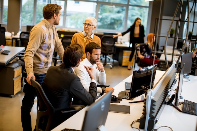シニアの実業家と若いビジネスマンは、近代的なオフィスで働く