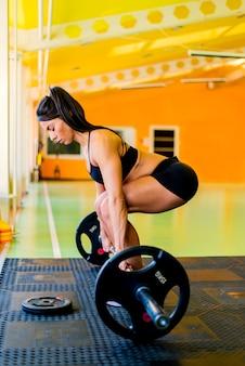 Молодая милая женщина держа весы и делая фитнес крытый