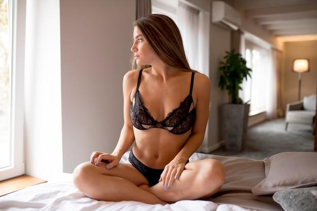 Сексуальная молодая женщина, сидя на кровати