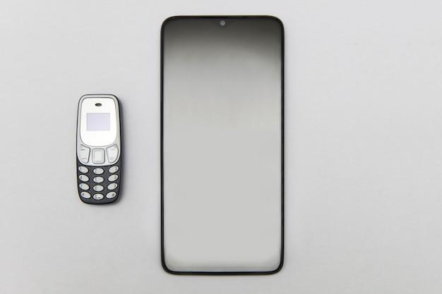 現代のスマートフォンと古い古典的な携帯電話が並んでいる