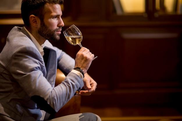 若い男が白ワインを試飲で見る