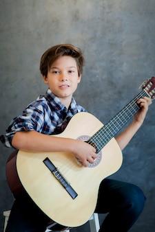 アコースティックギターを弾く十代の少年