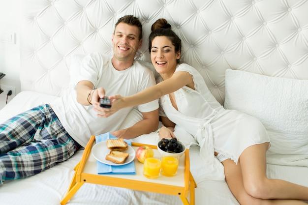 ベッドで朝食を持っているカップル