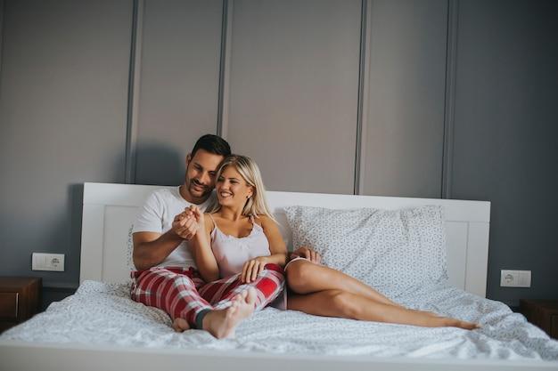 Ласковые любовники обнимаются на кровати у себя дома