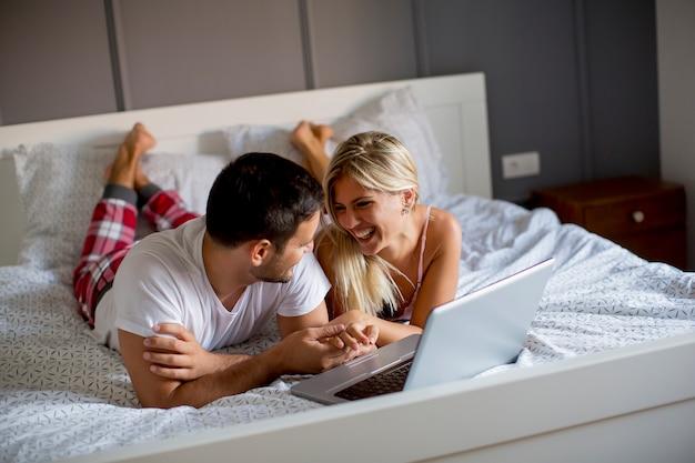 Интимные любовники с помощью ноутбука лежат на кровати в спальне