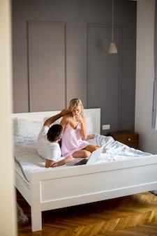 Интимные любовники с помощью ноутбука сидят на кровати в спальне