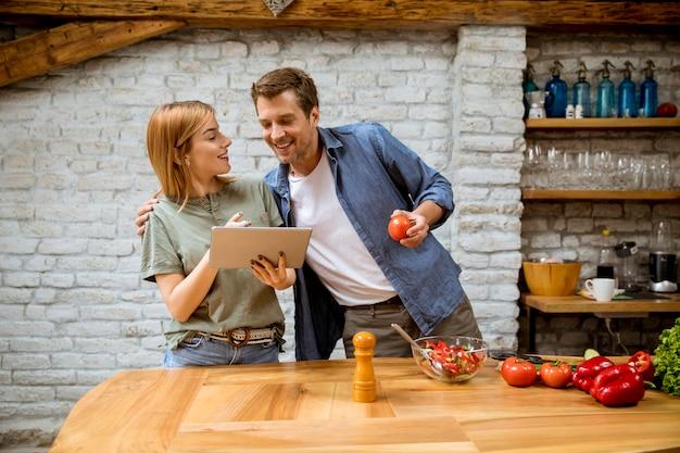 素敵な陽気な若いカップルが一緒に夕食を作って、デジタルタブレットでレシピを見て、素朴なキッチンで楽しんで