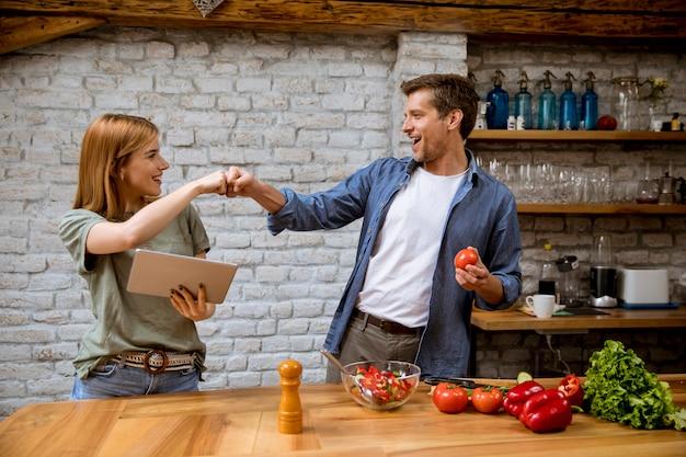 Прекрасная веселая молодая пара готовит обед вместе, смотрит рецепт на цифровой планшет и развлекается на деревенской кухне