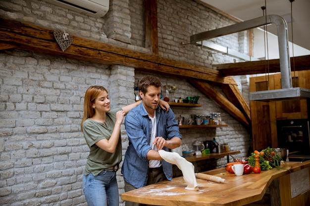 Прекрасная веселая молодая пара готовит обед вместе и развлекается на деревенской кухне