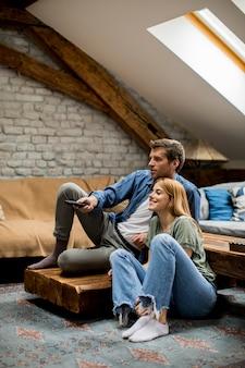 笑顔の素敵な若いカップルリラックスして自宅でテレビを見て