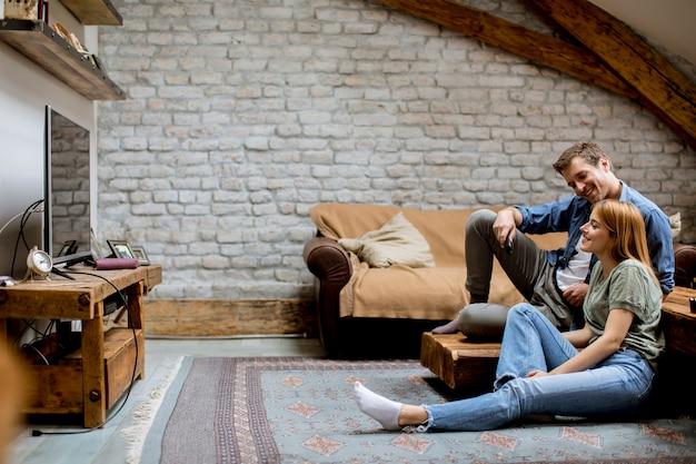 Улыбка прекрасной молодой пары, расслабляющейся и смотрящей телевизор дома