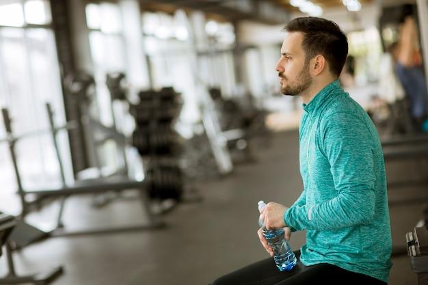 Спортсмен пьет воду из бутылки в спортзале и отдыхает
