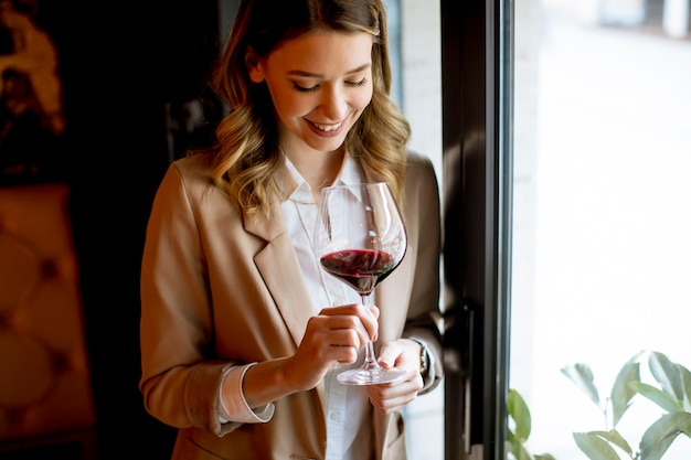 窓の近くに立って、よそ見赤ワインのグラスを持つ単一のかなり若い女性