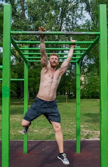 Сильный молодой человек упражнения в парке