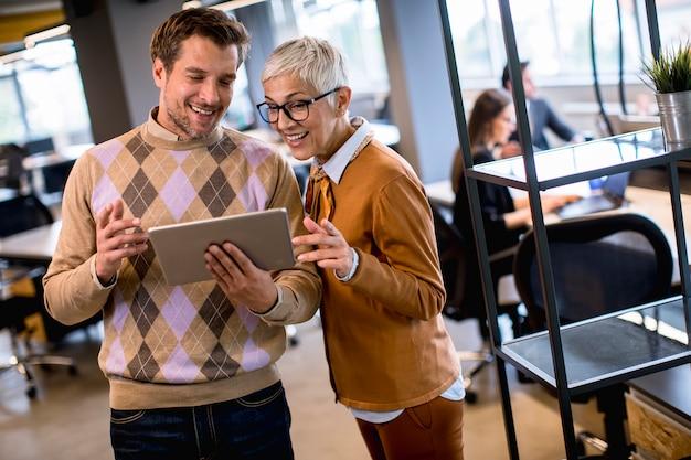 シニアビジネスの女性と彼女の若い同僚がデジタルタブレットでオフィスに立っています。