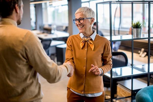 若いビジネスマンとオフィスで握手シニアビジネス女性