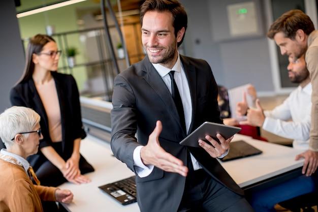 Молодой бизнесмен используя цифровую таблетку в офисе