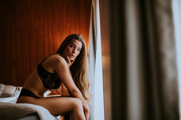 ベッドに横になっているランジェリーの魅力的なセクシーな女性