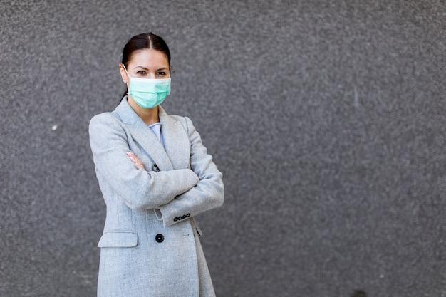 路上で保護マスクを持つかなり若い女性