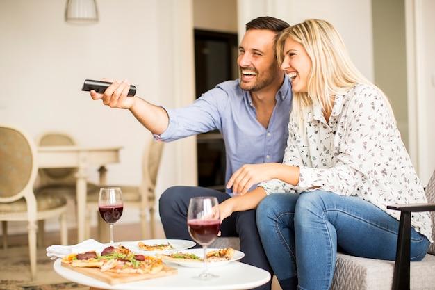Молодая пара, наслаждаясь есть пиццу и смотреть телевизор дома