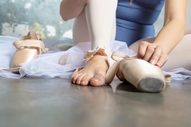 グランジの壁で床に座っている若いバレリーナ