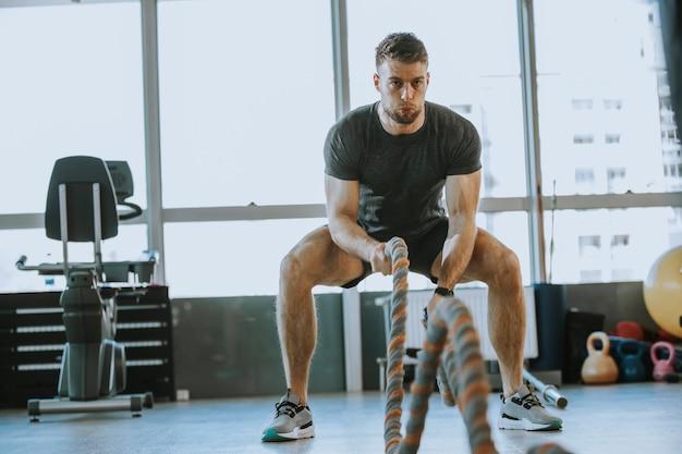 Молодой человек тренируется с боевыми канатами в тренажерном зале