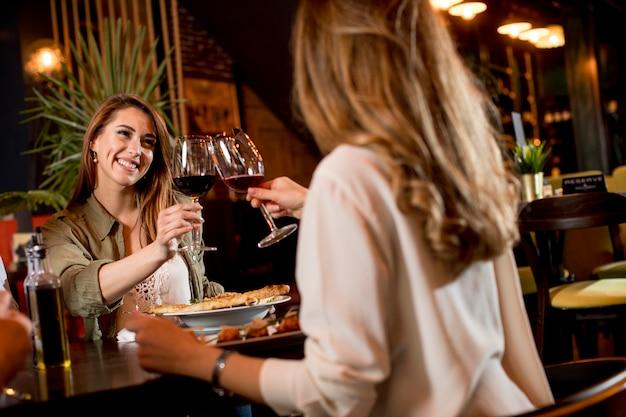 軽い夕食時にレストランで赤ワインを飲んで幸せな女性