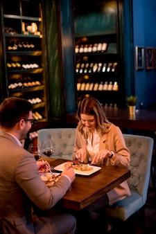 レストランで夕食を食べていると赤ワインを飲む若いカップル