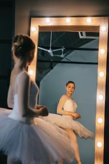 スタジオで踊る白いドレスでエレガントなバレリーナ